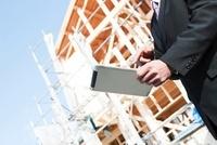 建設現場とタブレットPCを持つ男性