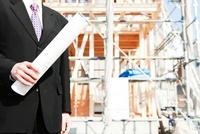 建設現場と図面を持つ男性