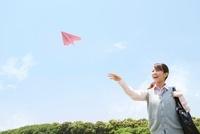 紙飛行機を投げる女子高生
