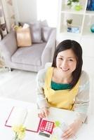 家計簿をつけている笑顔の女性