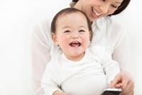 母親に抱っこされる赤ちゃんとスマートフォン