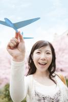 紙飛行機を持つ女性