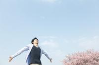桜と深呼吸する男性