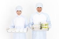食品を持っている食品衛生服の2人