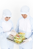 食品を調べている食品衛生服の2人
