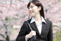 桜の前に立つビジネスウーマン