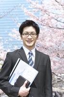 桜の前に立つビジネスマン