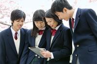 タブレットPCを見る男女学生4人