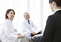 座って話す医師とビジネスウーマン