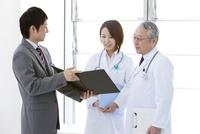 医師2人に書類を見せるビジネスマン