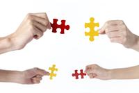 ジグソーパズルのピースを持つ2人の手