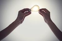 電球を持つ2人の手
