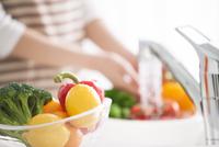 食材とキッチンで食材を洗う女性の手元