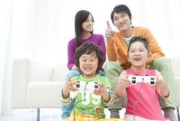 テレビゲームをしている家族4人