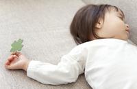四つ葉のクローバーを持って眠る赤ちゃん