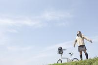 自転車と腕を広げる女子高生