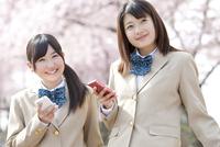 スマートフォンを持つ女子高生2人