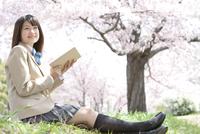 芝生に座って本を読む女子高生
