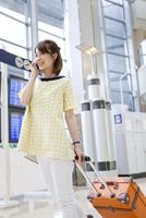 空港で電話をしながら歩く女性