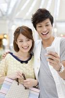 携帯電話で写真を撮るカップル