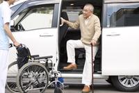 車から降りる杖をつく中高年男性