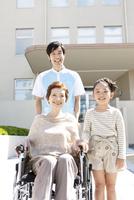 男性介護士と車いすに乗った中高年女性と孫