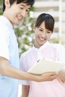 タブレットPCを見る男女介護士2人