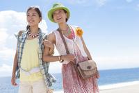 腕を組んで海岸を散歩する女性2人