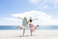 海岸でポーズをとる女性2人の後姿