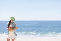 海岸でウクレレを演奏している女性