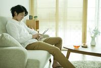 ソファーでタブレットPCを操作する男性