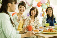 パーティーテーブルを囲む若い女性4人
