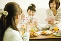 トランプで遊ぶ若い女性3人