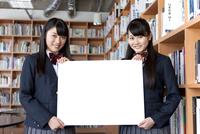 メッセージボードを持つ女子高校生2人