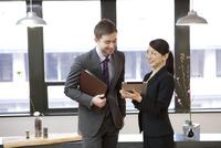 タブレットPCを見て話すビジネスマンとビジネスウーマン