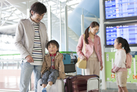 空港で旅行カバンを持つ4人家族