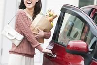 車のドアを開ける笑顔の女性