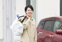 買い物袋を持っている笑顔の男性