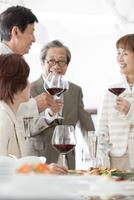 ワインを持ち談笑する中高年男女