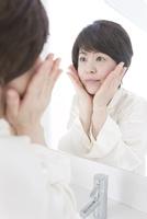 鏡を見る中高年女性