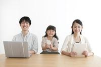 ノートパソコンとスマートフォンとタブレットPCを使う3人家族