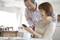 スマートフォンを見て話す中高年夫婦