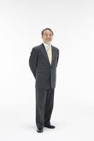 立って微笑むスーツ姿の中高年男性