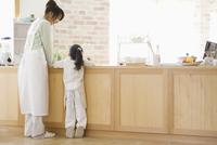キッチンに立つエプロン姿の母と娘の後ろ姿 07800043741| 写真素材・ストックフォト・画像・イラスト素材|アマナイメージズ