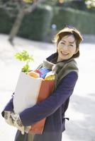 買い物袋を持つ中高年女性