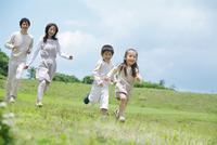芝生を走る4人家族