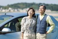車にもたれる中高年夫婦