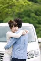 車の前で抱き合うカップル