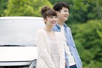 車の前に立つカップル