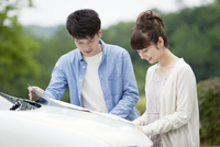 車の前で地図を見るカップル